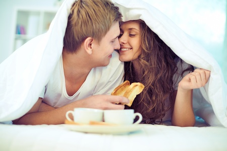 another: Couple enjoying one another while having breakfast in bed