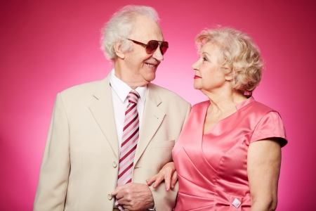 Affectionate seniors standing arm-in-arm and looking at each other photo