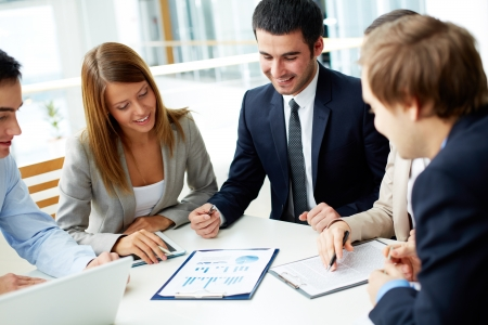 consulting team: Image of business partners discussing documents at meeting