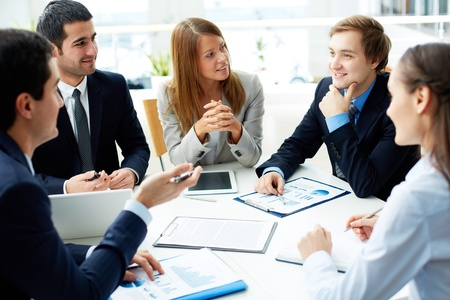 Image of business partners discussing documents and ideas at meeting photo