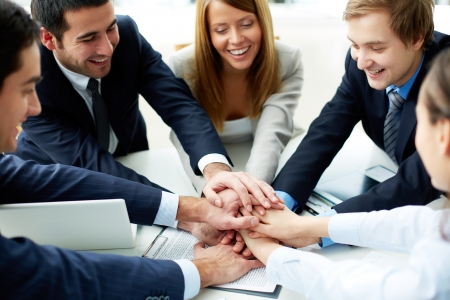trust people: Image of business partners making pile of hands at meeting Stock Photo