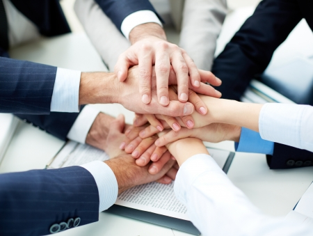 join the team: Close-up of business partners making pile of hands at meeting