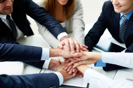 Close-up of business partners making pile of hands at meeting Stock Photo - 17533823