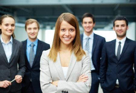 group leader: Group of friendly businesspeople with happy female leader in front Stock Photo