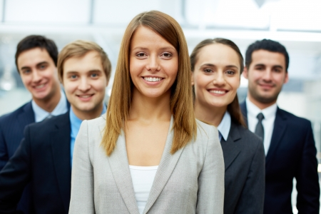 gorgeous businesswoman: Happy businesswoman looking at camera with smart associates behind Stock Photo