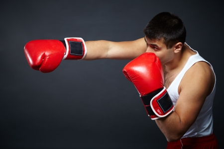 Portrait of young man in red boxing gloves fighting in isolation photo