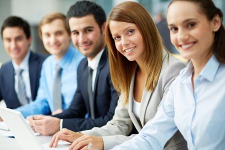 entreprise: Les gens d'affaires assis dans une rangée et de travail, se concentrer sur jolie femme