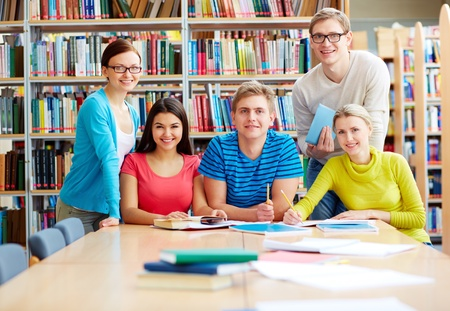 highschool student: Portrait of group of students sitting in college library and doing homework Stock Photo