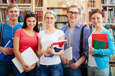 learner: Portrait of friendly students looking at camera in college library Stock Photo