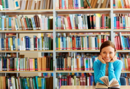 bibliotecas: Retrato de estudiante inteligente con el libro abierto de lectura en biblioteca universitaria