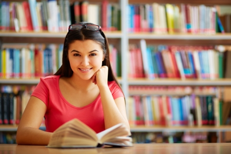 library student: Portrait of cute girl with open book looking at camera in college library Stock Photo
