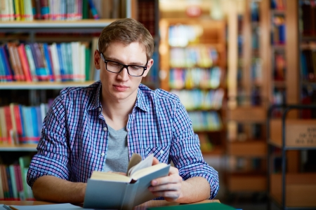Portrait of clever student with open book reading it in college library Stock Photo - 17534421