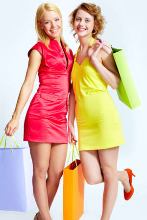Two beautiful shoppers with paperbags over white background Stock Photo - 17534329