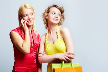 Gorgeous ladies looking at something while shopping, one girl talking by the phone Stock Photo - 17534367