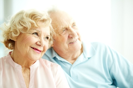 senior female: Close-up portrait of a charming elderly woman with her husband on background Stock Photo