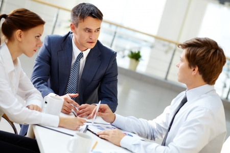 Seus boss looking at one of his employees and listening to him at meeting  Stock Photo - 17533621