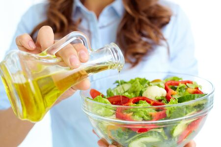 Close-up of female pouring oil into vegetable salad in glass bowl photo