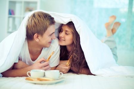 marido y mujer: Pareja disfrutando de unos a otros mientras que el desayuno en la cama Foto de archivo