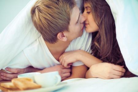 enamorados besandose: Joven pareja amorosa besándose bajo la manta