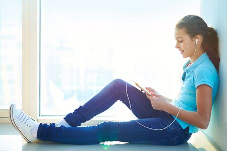 Lovely girl listening to the music during the break at school Stock Photo - 17622161