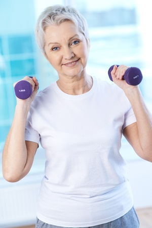 senior fitness: Portrait of pretty senior woman exercising with dumbbells