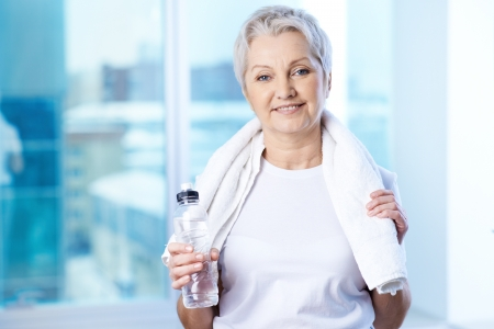 senior adult woman: Portrait of pretty senior woman with bottle of water in gym  Stock Photo