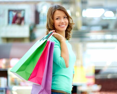 shopping girl: Smiling young woman posing with a handful of shopping bags Stock Photo