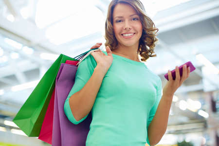 shopaholism: Portrait of a pretty lady spending her weekend in a shopping center