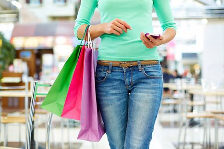 personal shopper: Close-up shot of a modern shopper with a mobile phone and colorful shopping bags