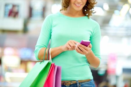 笑顔の女性の買い物をしていると、途中でテキスト メッセージ