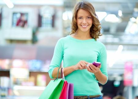 shopaholism: Portrait of a smiling shopper sending a text message Stock Photo