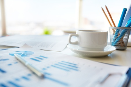 office stationery: Close-up image of an office desk at morning with a cup of tea and financial documents