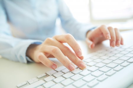 inputting: Female office worker typing on the keyboard
