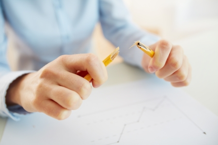 unrecognized: Stressed business worker releasing tension by breaking a pencil Stock Photo