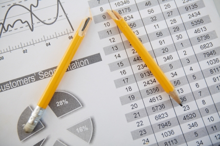 Close-up shot of a broken pencil lying over printed statistics Stock Photo - 17640024
