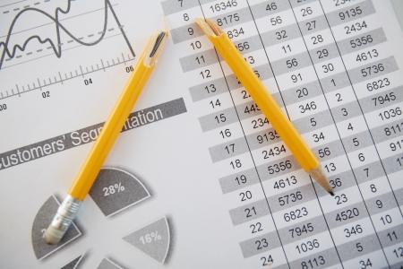 statistical: Close-up shot of a broken pencil lying over printed statistics
