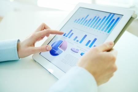 Business persona analizzando statistiche finanziarie visualizzate sullo schermo del tablet