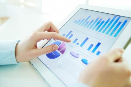 Close-up beeld van een kantoor werknemer met behulp van een touchpad om statistische gegevens te analyseren