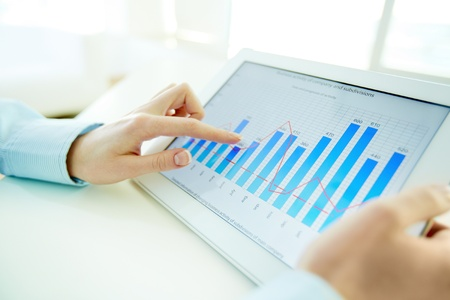 statistical: Experienced manager reviewing annual report presented on the screen of the pad Stock Photo