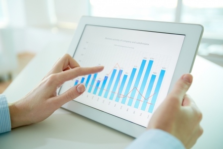 Female worker analyzing financial results with the help of a digital pad Stock Photo