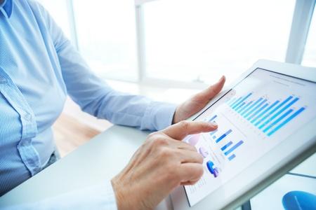 recursos financieros: Imagen de la mano humana que se�ala en la pantalla t�ctil con el documento de negocios