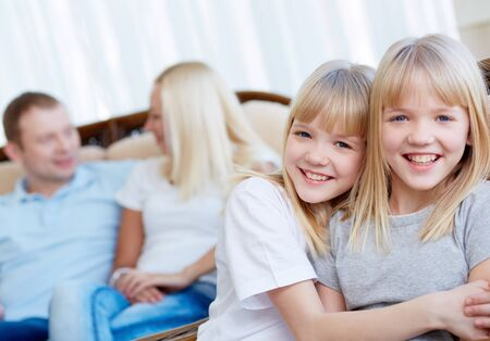 Portrait of happy twin girls looking at camera with their parents behind Stock Photo - 17622332