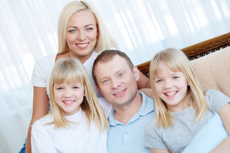 Portrait of happy family with twin daughters smiling at camera  Stock Photo - 17622356