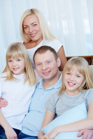 Portrait of happy family with twin daughters smiling at camera  Stock Photo - 17622351