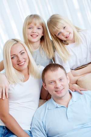 Portrait of happy couple with twin daughters smiling at camera  Stock Photo - 17622312