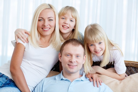 Portrait of happy couple with twin daughters resting at home Stock Photo - 17622314