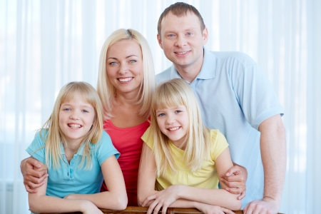 Portrait of happy couple with twin daughters looking at camera at home Stock Photo - 17622340