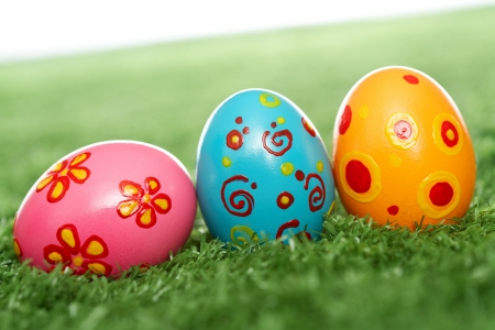 Row of colored and decorated Easter eggs in grass photo