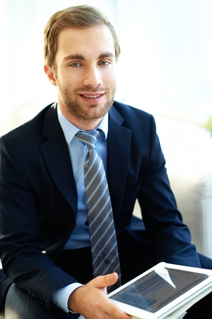 principal: Portrait of attractive businessman with touchpad looking at camera