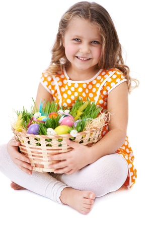 Photo of cute girl looking at camera while holding basket with colorful Easter eggs photo